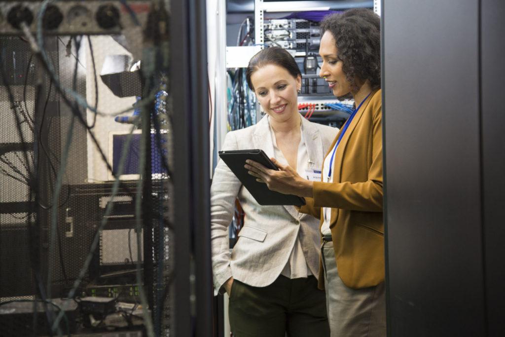 Mature adult women in data center programing mainframe through digital tablet. Team meeting in server room.