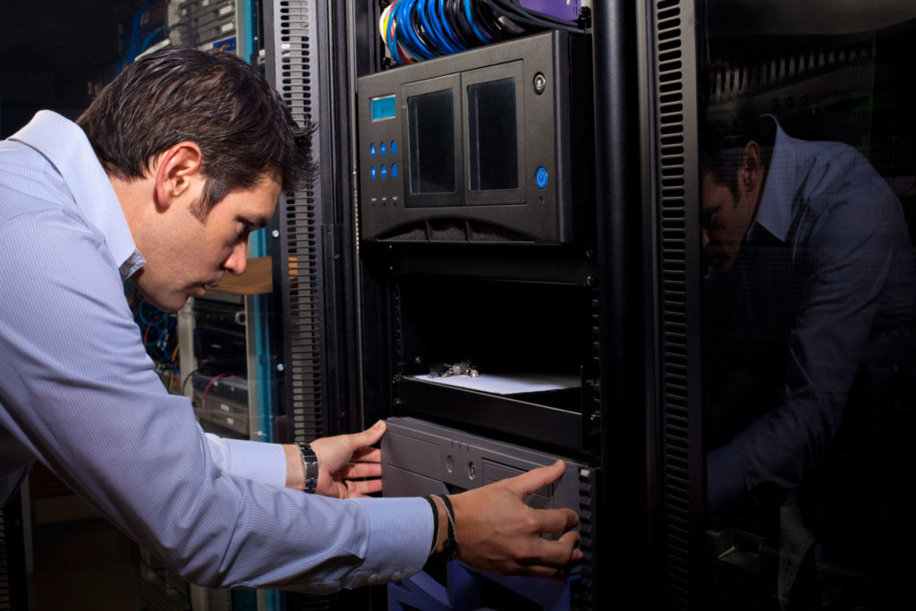 IT Systems Administrator Installing Computer Equipment in Server Room